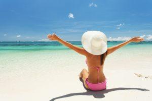 Cirurgia plástica e autoestima: mulher sentada de costas na praia e de frente para o mar, com os braços abertos