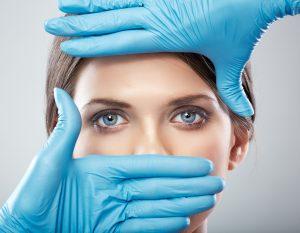 Mãos com luvas de cirurgia plástica enquadrando o rosto de uma mulher