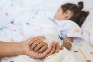 Adulto segurando na mão de criança no hospital. A criança tem um soro na mão.