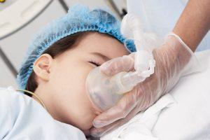 Momentos antes de cirurgias em crianças. Uma pessoa adulta está segurando um aparelho de nebulização no rosto de uma criança.