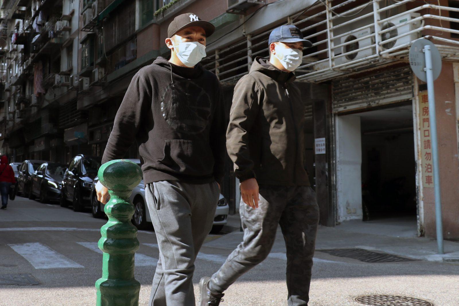 Duas pessoas agasalhadas andando lado a lado na rua com máscaras faciais.