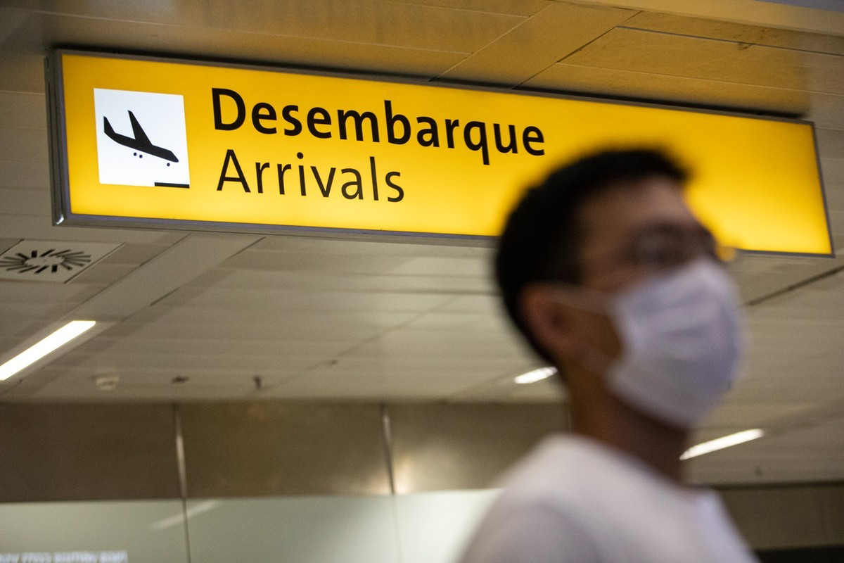 Turista na área de desembarque no aeroporto com máscara facial para evitar o coronavírus.